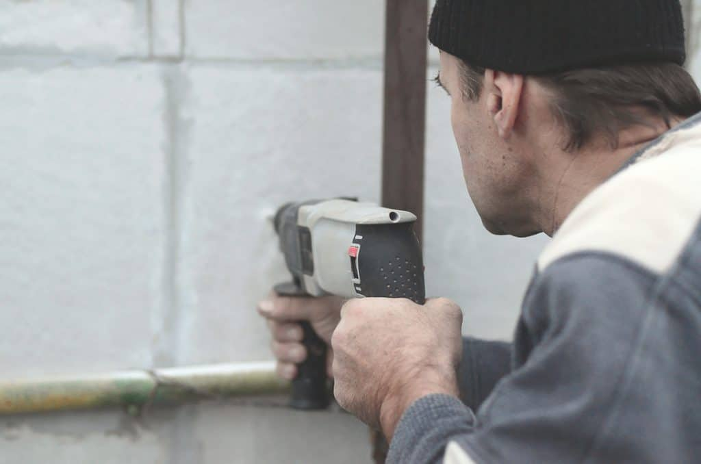Cavity wall insulation Worker drilling holes in wall prior to cavity wall insulation beads being injected